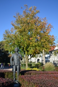 JMU's statue of James Madison standing in front of autumn-colored tree